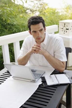 Man contemplating while using laptop photo