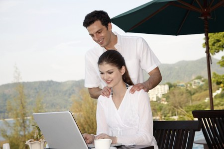 Woman using laptop, man watching from behind photo