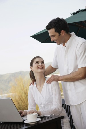 Woman smiling and looking at man while using laptop photo