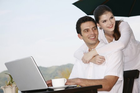 Man using laptop, woman hugging man from behind photo