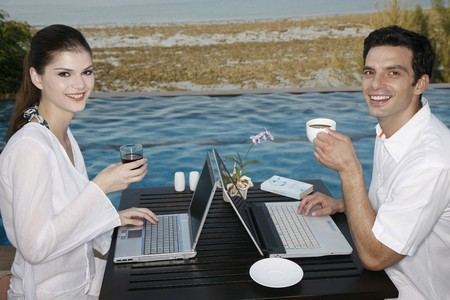 Man and woman drinking while using laptop photo