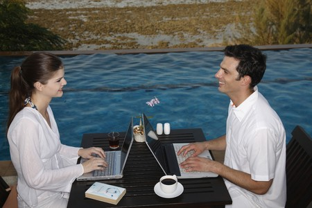 Man and woman using laptop by the pool side photo