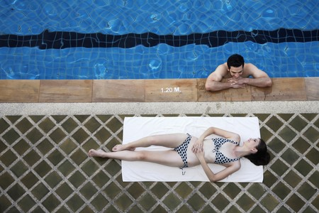 southeastern european descent: Man in swimming pool flirting with woman