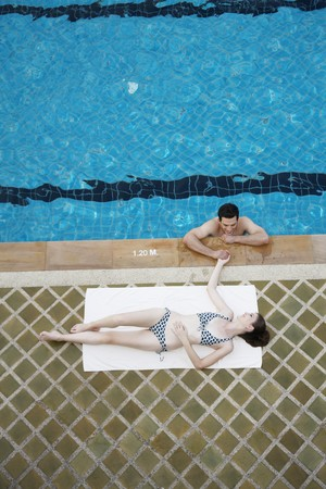 Man in swimming pool flirting with woman Stock Photo - 7447014