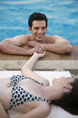 Man in swimming pool flirting with woman Stock Photo - 7446810