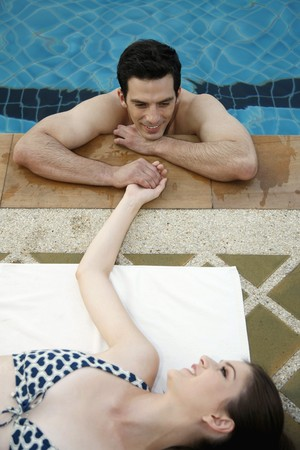 Man in swimming pool flirting with woman Stock Photo - 7446842