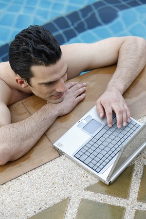 southeastern european descent: Man on edge of swimming pool with laptop