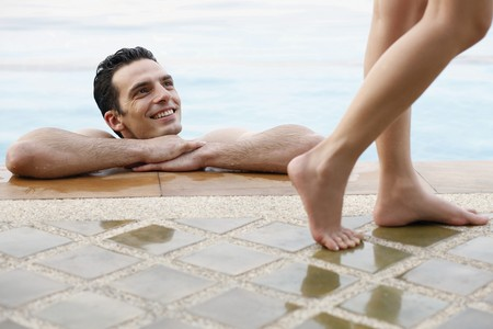 Man in pool looking at woman walking by Stock Photo