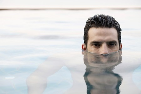 Man in pool, head half submerged in water photo