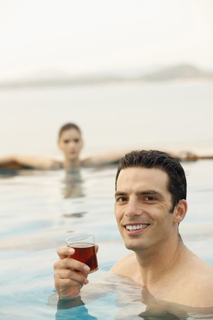 southeastern european descent: Man in pool with a glass of tea, woman relaxing in the background