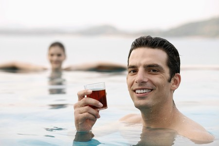 Man in pool with a glass of tea, woman relaxing in the background Stock Photo - 7445911