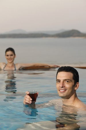 Man in pool with a glass of tea, woman relaxing in the background photo