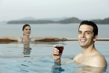 Man in pool with a glass of tea, woman relaxing in the background Stock Photo - 7445983