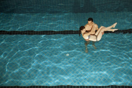 Man carrying woman in swimming pool photo