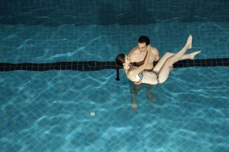carrying girlfriend: Man carrying woman in swimming pool