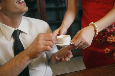tomando refresco: Hombre de negocios de servir de mujer con una taza de t�  Foto de archivo