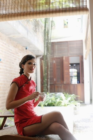 Woman in cheongsam with a cup of tea Stock Photo - 7446031