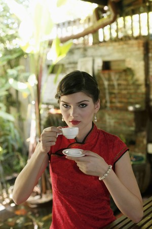 Woman in cheongsam drinking tea Stock Photo - 7446521
