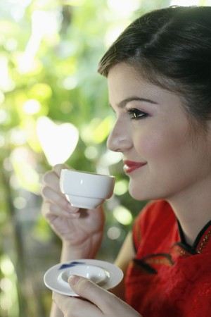Woman in cheongsam drinking tea Stock Photo - 7446180