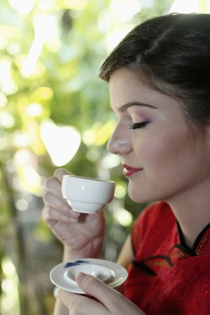 Woman in cheongsam drinking tea photo