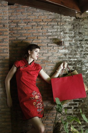 Woman in cheongsam carrying shopping bags Stock Photo - 7447011
