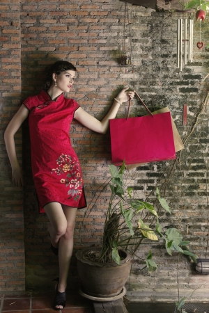 cheongsam: Woman in cheongsam carrying shopping bags