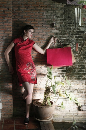 Woman in cheongsam carrying shopping bags photo