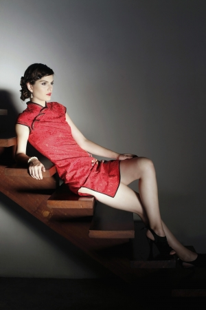 southeastern european descent: Woman in cheongsam posing on the stairs