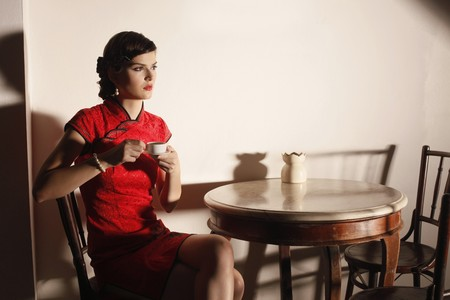 Woman in cheongsam with a cup of tea photo