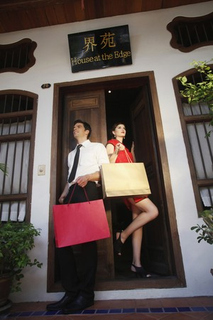 Man and woman with shopping bags standing at the doorway photo