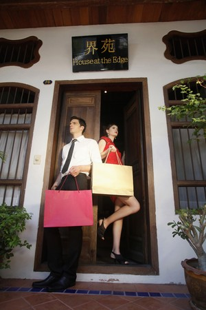 Man and woman with shopping bags standing at the doorway Stock Photo - 7446480