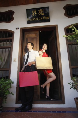 Man and woman with shopping bags standing at the doorway Stock Photo - 7446383