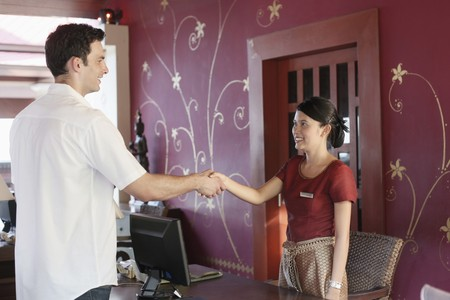 Man shaking hands with hotel receptionist photo