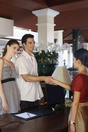 Man shaking hands with hotel receptionist, woman smiling while watching Stock Photo - 24303188