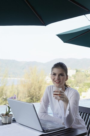 Woman holding a glass of tea and sitting in front of a laptop Stock Photo - 7445921
