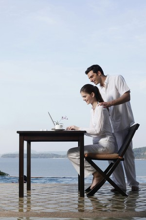 Woman using laptop by the pool side, man watching from behind photo