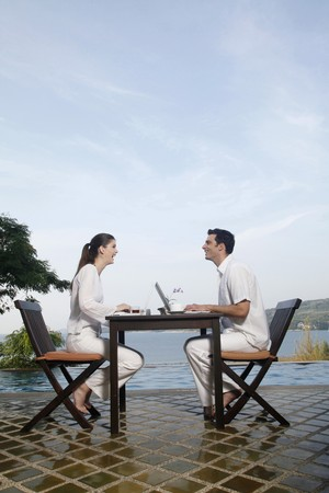 Man and woman laughing while using laptop Stock Photo - 7446933