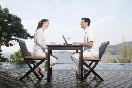 boy sitting: Man and woman using laptop by the pool side