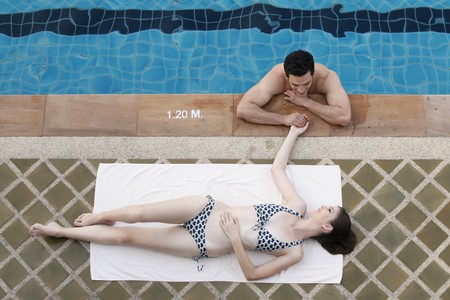Man in swimming pool flirting with woman Stock Photo - 7446973