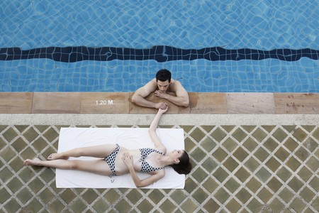 Man in swimming pool flirting with woman photo