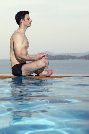 Man meditating by edge of swimming pool photo