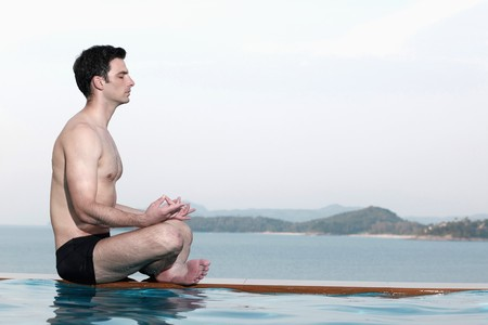 man meditating: Man meditating by edge of swimming pool