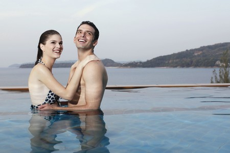 Man and woman embracing in swimming pool Stock Photo