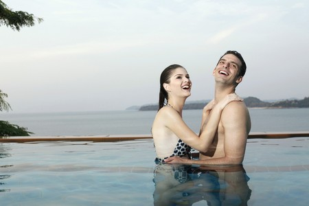 Man and woman embracing in swimming pool photo