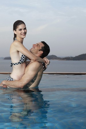 Man lifting up woman in swimming pool photo