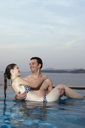 Man carrying woman in his arms in swimming pool photo