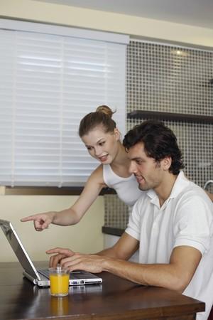 Man using laptop, woman pointing at laptop Stock Photo - 7446193