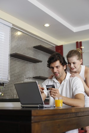 Man holding credit card and using laptop, woman watching from behind Stock Photo - 7446083