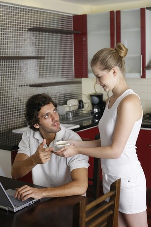 Woman serving man a cup of coffee, man using laptop photo