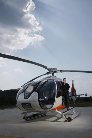 Businesswoman standing at the side of helicopter photo